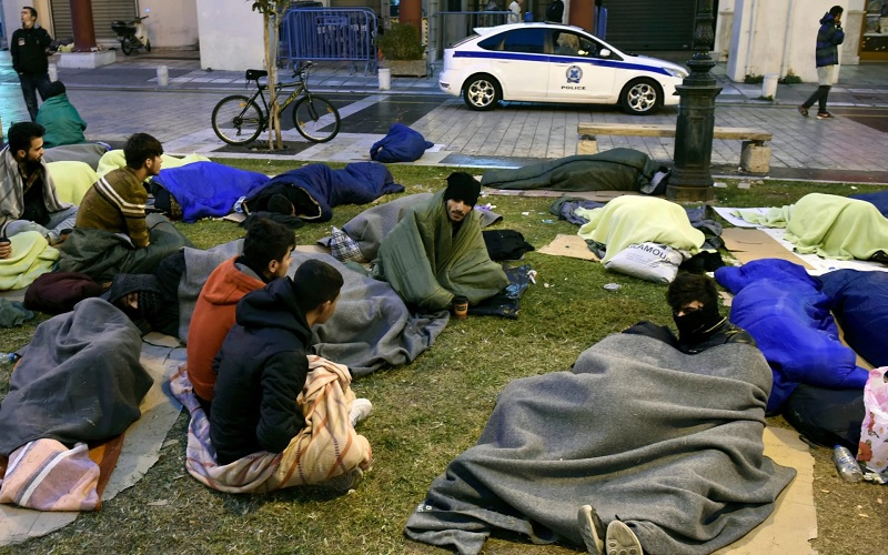 Refugees line up outside police station in Greece waiting to be arrested in order to claim asylum